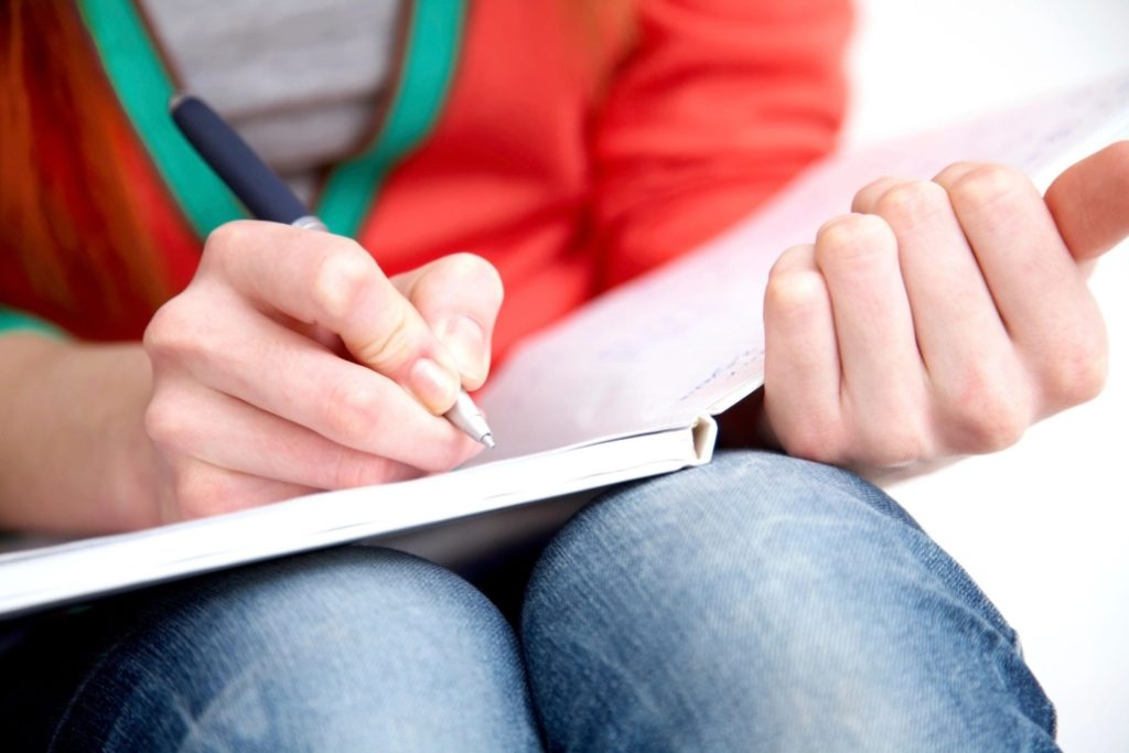 female hands writing in journal